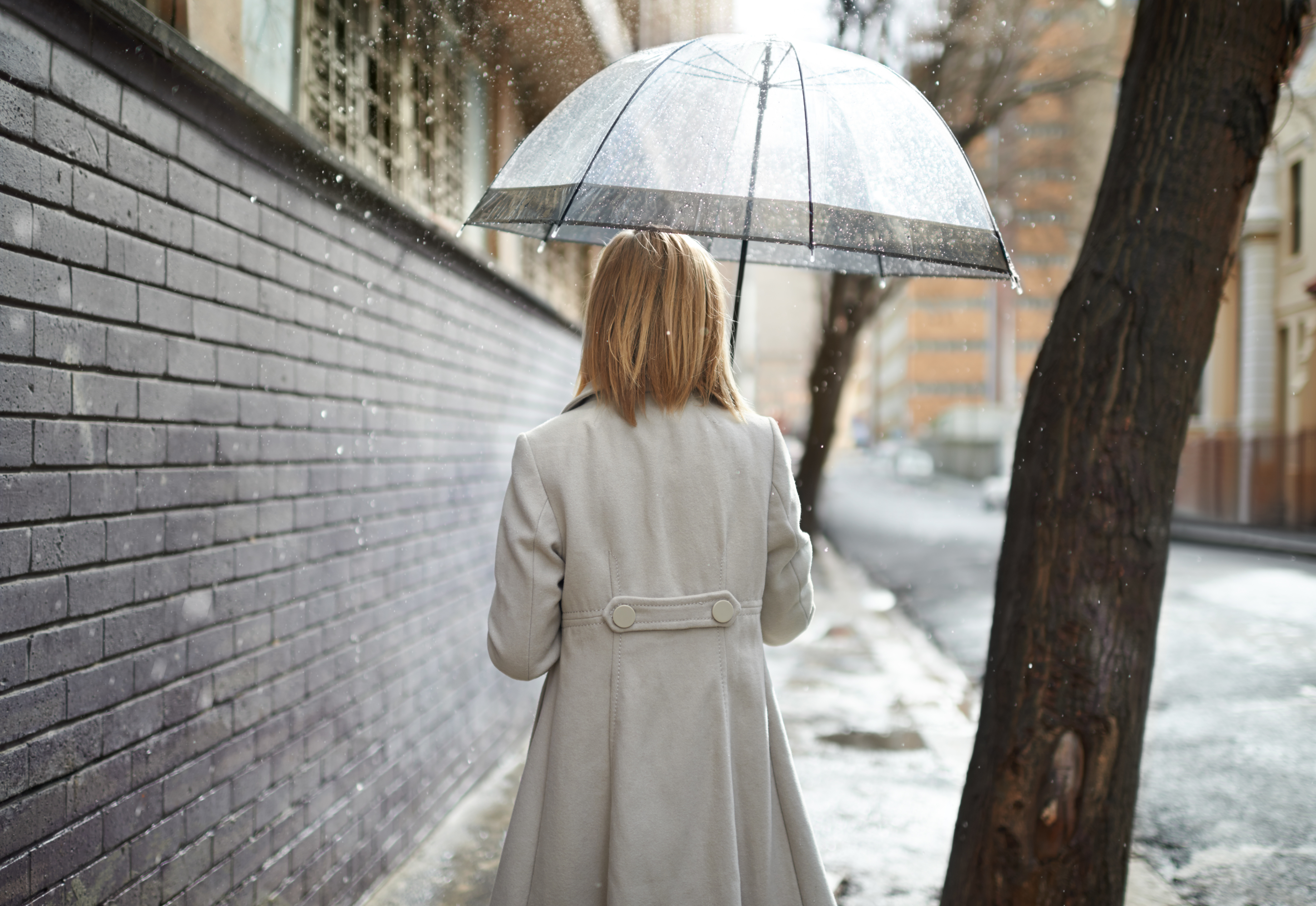 Rearview shot of a woman walking down a street in the rain and holding an umbrella